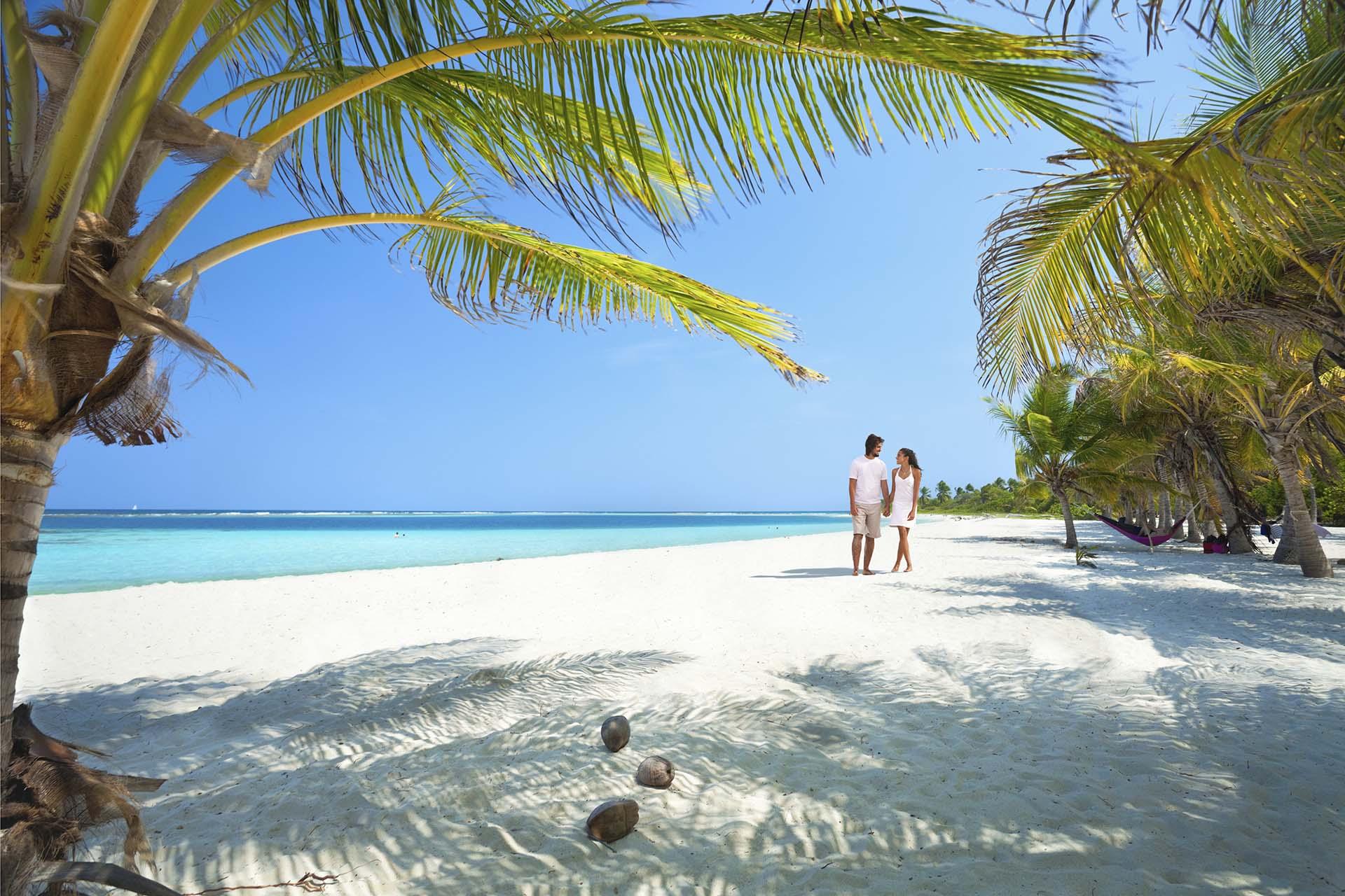 Una joven pareja caminando a lo largo de una solitaria playa de una isla tropical
