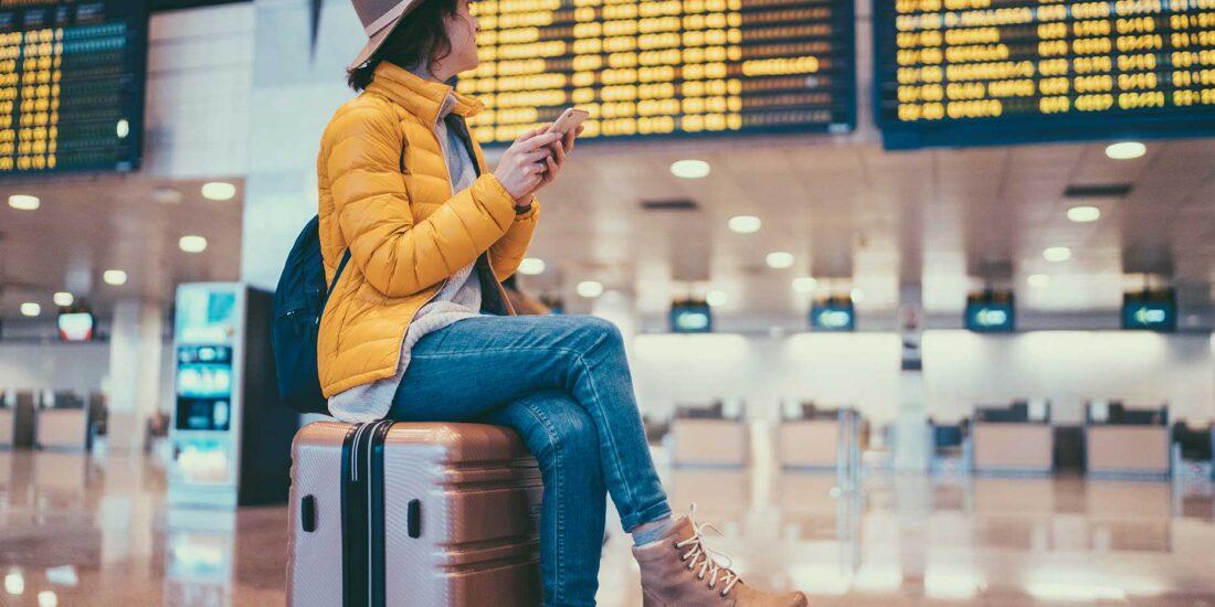 mujer sentada sobre maleta y buscando su vuelo
